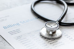 Déclaration de facturation de soins de santé avec le stéthoscope du ` s de docteur sur le fond en pierre image libre de droits