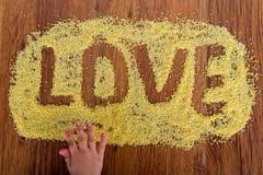 Déclaration de millet peint par amour L'enfant dessine sur une table avec le millet de croustillants Photo libre de droits
