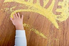 Déclaration de millet peint par amour L'enfant dessine sur une table avec le millet de croustillants Photographie stock