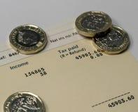 Déclaration de revenu personnel montrant des chiffres de revenu et d'impôts pour la déclaration d'impôt BRITANNIQUE Images stock