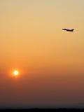 Décollage d'aéronefs au coucher du soleil Photographie stock