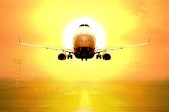 Décollage d'avions de transport de passagers sur la piste de l'aéroport dans le coucher du soleil Photographie stock libre de droits