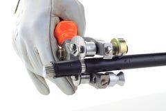 Décolleur de prise de la main de l'homme et câble à haute tension Photographie stock libre de droits