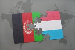 déconcertez avec le drapeau national de l'Afghanistan et du Luxembourg sur un fond de carte du monde Images libres de droits