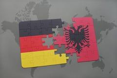 déconcertez avec le drapeau national de l'Allemagne et de l'Albanie sur un fond de carte du monde Photos libres de droits