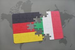 déconcertez avec le drapeau national de l'Allemagne et de l'Italie sur un fond de carte du monde Photo libre de droits