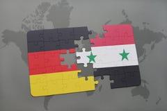 déconcertez avec le drapeau national de l'Allemagne et de la Syrie sur un fond de carte du monde Photos libres de droits