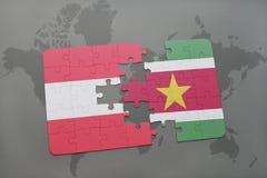 déconcertez avec le drapeau national de l'Autriche et du Surinam sur un fond de carte du monde Photos stock