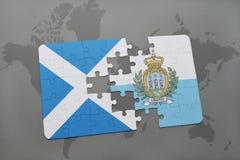 déconcertez avec le drapeau national de l'Ecosse et du Saint-Marin sur un fond de carte du monde Photo libre de droits