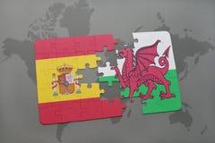 déconcertez avec le drapeau national de l'Espagne et du Pays de Galles sur un fond de carte du monde Photos stock