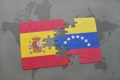déconcertez avec le drapeau national de l'Espagne et du Venezuela sur un fond de carte du monde Images stock