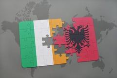 déconcertez avec le drapeau national de l'Irlande et de l'Albanie sur un fond de carte du monde Image libre de droits
