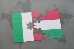 déconcertez avec le drapeau national de l'Italie et de la Hongrie sur un fond de carte du monde Photos stock