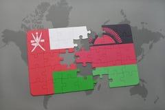 déconcertez avec le drapeau national de l'Oman et du Malawi sur un fond de carte du monde Photographie stock