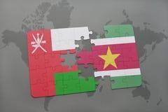 déconcertez avec le drapeau national de l'Oman et du Surinam sur un fond de carte du monde Photographie stock