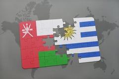 déconcertez avec le drapeau national de l'Oman et de l'Uruguay sur un fond de carte du monde Photos libres de droits