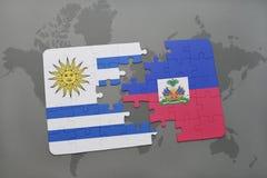 déconcertez avec le drapeau national de l'Uruguay et du Haïti sur un fond de carte du monde Photos stock