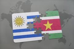 déconcertez avec le drapeau national de l'Uruguay et du Surinam sur un fond de carte du monde Image stock