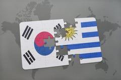 déconcertez avec le drapeau national de la Corée du Sud et de l'Uruguay sur un fond de carte du monde Photographie stock libre de droits
