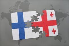 déconcertez avec le drapeau national de la Finlande et de la Géorgie sur un fond de carte du monde Photographie stock libre de droits