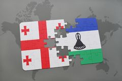 déconcertez avec le drapeau national de la Géorgie et du Lesotho sur une carte du monde Photographie stock libre de droits