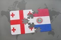 déconcertez avec le drapeau national de la Géorgie et du Paraguay sur une carte du monde Images stock