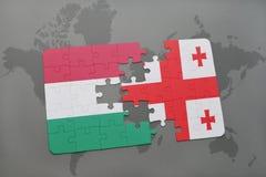 déconcertez avec le drapeau national de la Hongrie et de la Géorgie sur un fond de carte du monde Photographie stock