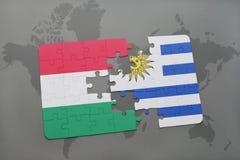 déconcertez avec le drapeau national de la Hongrie et de l'Uruguay sur une carte du monde Images libres de droits