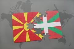 déconcertez avec le drapeau national de la Macédoine et du pays Basque sur un fond de carte du monde Photographie stock libre de droits