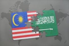 déconcertez avec le drapeau national de la Malaisie et de l'Arabie Saoudite sur un fond de carte du monde Photographie stock