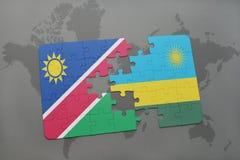 déconcertez avec le drapeau national de la Namibie et du Rwanda sur une carte du monde Photographie stock libre de droits