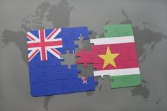 déconcertez avec le drapeau national de la Nouvelle Zélande et du Surinam sur un fond de carte du monde Photos libres de droits