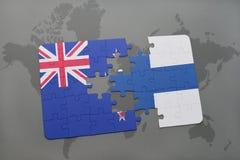 déconcertez avec le drapeau national de la Nouvelle Zélande et de la Finlande sur un fond de carte du monde Images libres de droits