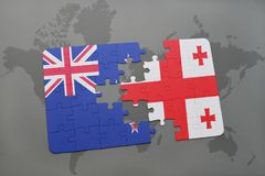 déconcertez avec le drapeau national de la Nouvelle Zélande et de la Géorgie sur un fond de carte du monde Photo libre de droits