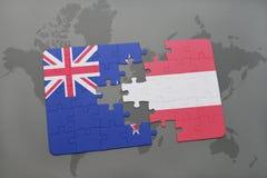 déconcertez avec le drapeau national de la Nouvelle Zélande et de l'Autriche sur un fond de carte du monde Photos stock