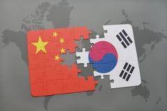 déconcertez avec le drapeau national de la porcelaine et de la Corée du Sud sur un fond de carte du monde Photos stock