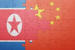 Déconcertez avec le drapeau national de la porcelaine et de la Corée du Nord image libre de droits