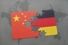 déconcertez avec le drapeau national de la porcelaine et de l'Allemagne sur un fond de carte du monde Image stock