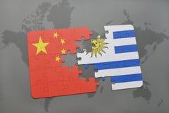 déconcertez avec le drapeau national de la porcelaine et de l'Uruguay sur un fond de carte du monde Photos libres de droits