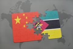 déconcertez avec le drapeau national de la porcelaine et de la Mozambique sur un fond de carte du monde Photographie stock