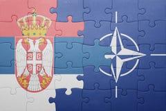 Déconcertez avec le drapeau national de la Serbie et de l'OTAN Photo stock