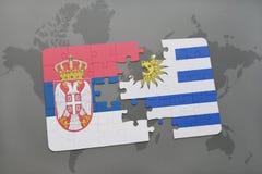 déconcertez avec le drapeau national de la Serbie et de l'Uruguay sur une carte du monde Photos stock