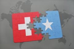 déconcertez avec le drapeau national de la Suisse et de la Somalie sur un fond de carte du monde Photos libres de droits