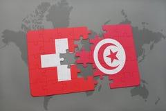 déconcertez avec le drapeau national de la Suisse et de la Tunisie sur un fond de carte du monde Photos stock