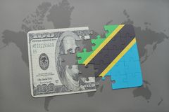 déconcertez avec le drapeau national de la Tanzanie et du billet de banque du dollar sur un fond de carte du monde Photos libres de droits