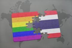 déconcertez avec le drapeau national de la Thaïlande et le drapeau gai d'arc-en-ciel sur un fond de carte du monde Photographie stock libre de droits