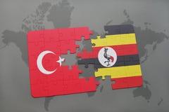 déconcertez avec le drapeau national de la Turquie et de l'Ouganda sur une carte du monde Photos stock