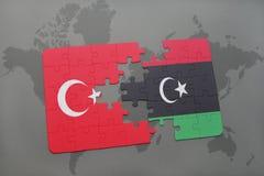 déconcertez avec le drapeau national de la Turquie et de la Libye sur une carte du monde Photos stock