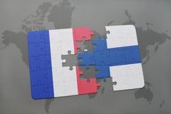 déconcertez avec le drapeau national des Frances et de la Finlande sur un fond de carte du monde Photos stock