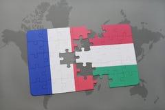 déconcertez avec le drapeau national des Frances et de la Hongrie sur un fond de carte du monde Photos stock